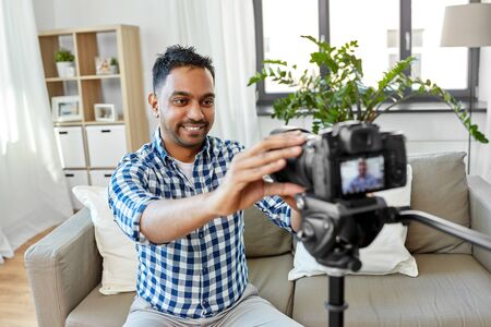 indian male video blogger adjusting camera at home