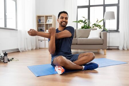 man training and stretching arm at home Reklamní fotografie