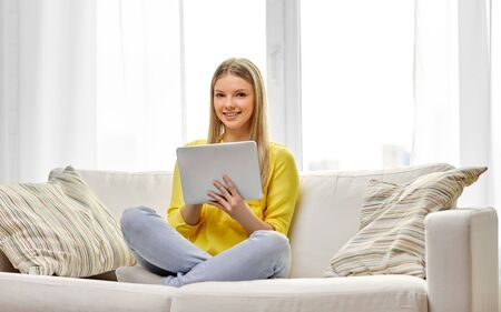 young woman or teenage girl with tablet pc at home