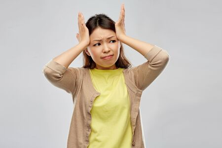 stressed asian woman holding to her head Banco de Imagens