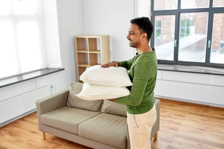 indian man with sofa cushions at new home 写真素材