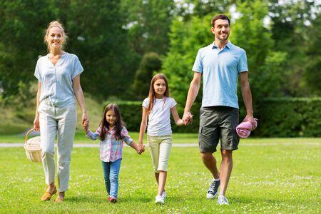famille avec panier de pique-nique marchant dans le parc d'été