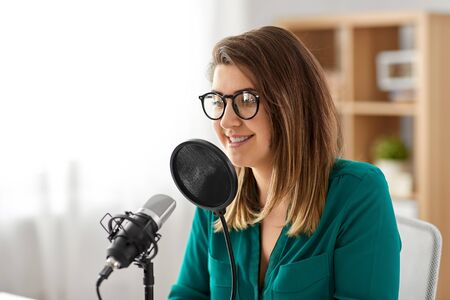 woman with microphone recording podcast at studio Imagens