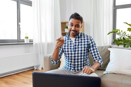 indian male blogger pointing to you at home