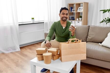 indian man checking takeaway food order at home