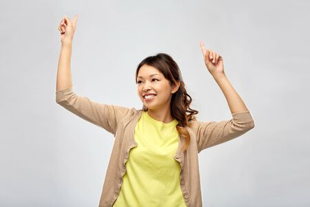 happy asian woman dancing over grey background