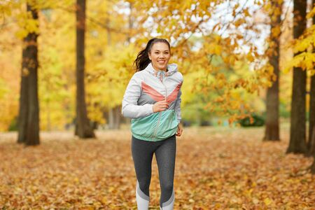 Young woman running in autumn park