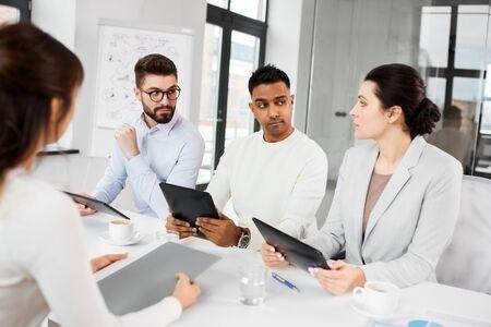 Nuevo concepto de trabajo, contratación y empleo: equipo internacional de reclutadores con tabletas con entrevista con empleada en la oficina