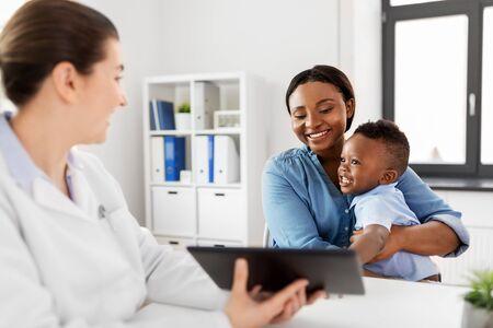 Madre con bebé y médico con tableta en clínica Foto de archivo