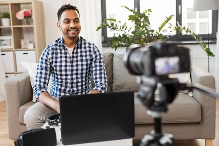 Male blogger with camera video blogging at home