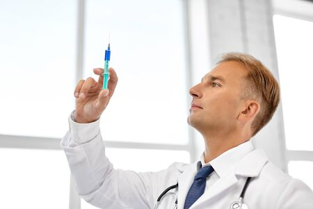 smiling doctor with syringe at hospital Stock Photo
