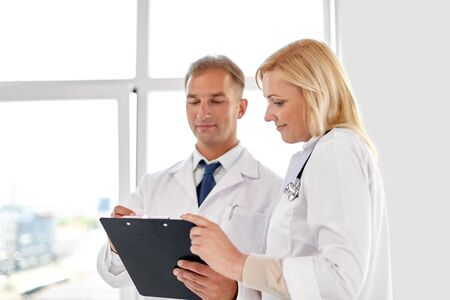 smiling doctors with clipboard at hospital Stock Photo