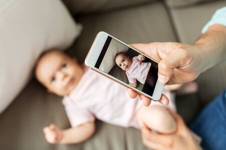 father with smartphone taking picture baby at home