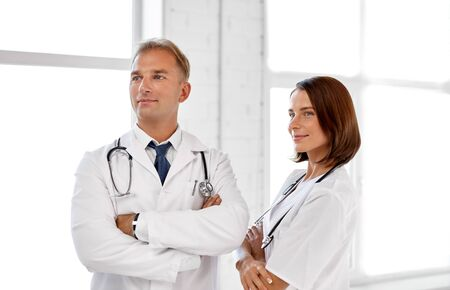 Smiling doctors in white coats at hospital