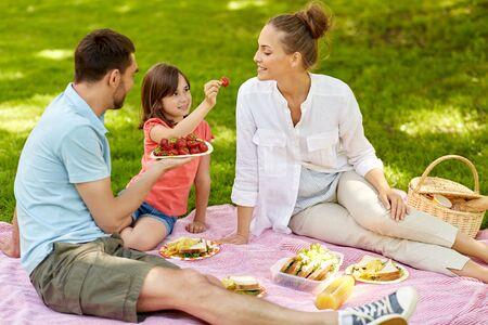 Familie die aardbeien eet op picknick in het park Stockfoto