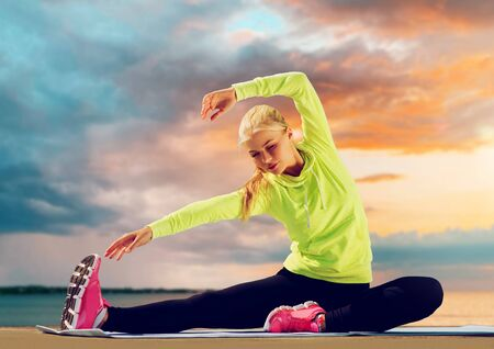 woman stretching on exercise mat at seaside