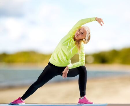 woman stretching on exercise mat on beach