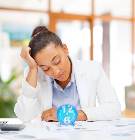 tired businesswoman with alarm clock at office