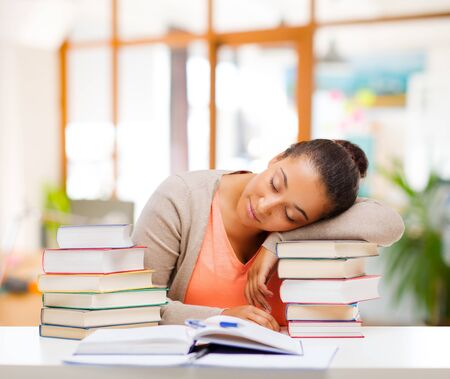 tired african female student sleeping on books