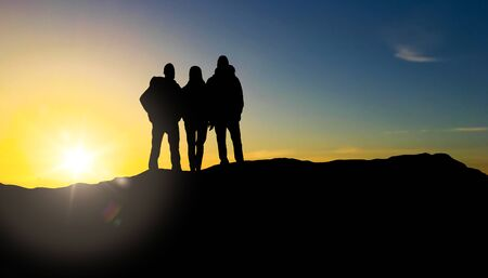 group of travellers with backpacks over sunrise Stock Photo