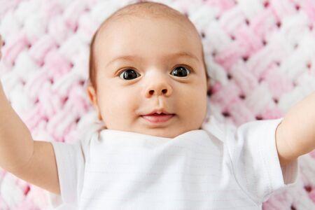 dolce bambina sdraiata su una coperta di peluche a maglia Archivio Fotografico