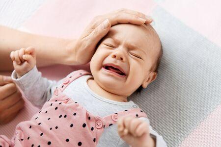 la mano della madre che si tocca piangendo la piccola bambina Archivio Fotografico