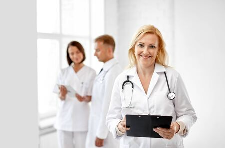 smiling doctor with clipboard and stethoscope Banco de Imagens