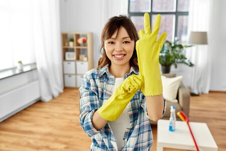 asian woman putting protective rubber gloves on