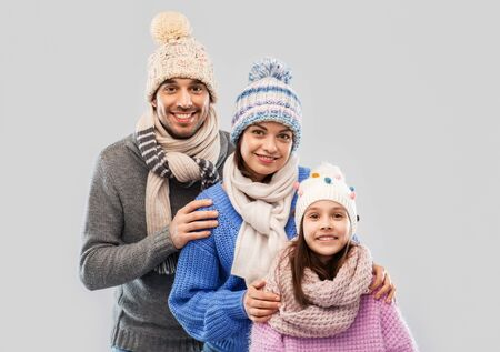 happy family in winter clothes on grey background Stockfoto