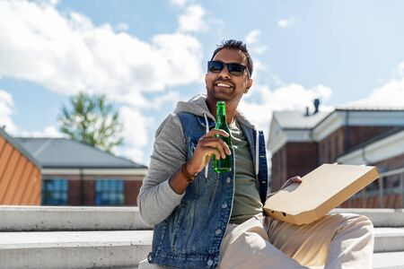 indian man with pizza and drinking beer outdoors Stock Photo - 127122658
