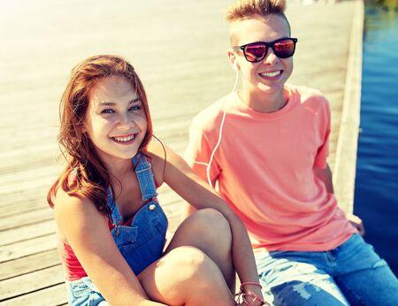 Happy teenage couple with earphones on river berth