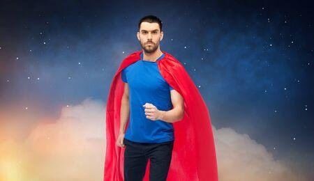 Man in red superhero cape over night sky