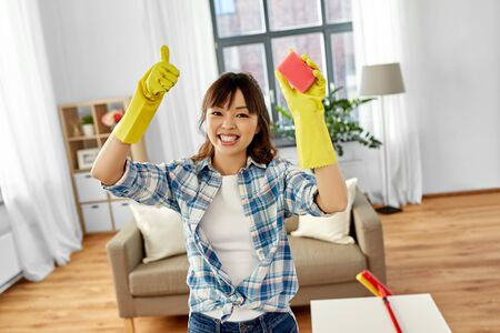 Happy Asian woman with sponge cleaning at home Banque d'images