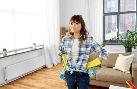 Asiatische Frau mit Lappen und Waschmittel, die nach Hause säubert