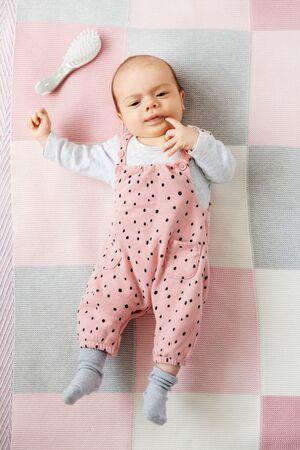 Sweet baby girl in pink suit lying on blanket