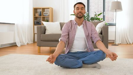 Man with tablet computer meditating at home Stock Photo