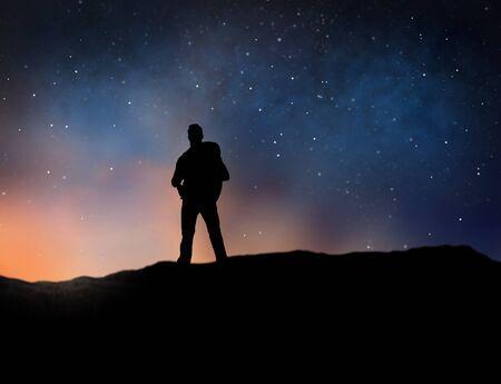 Traveler standing on edge over night sky