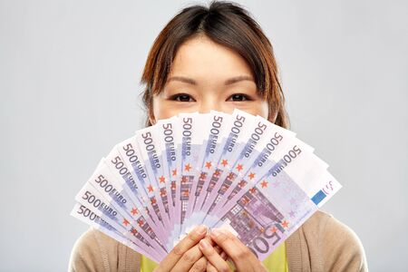 People, ethnicity and portrait concept - Happy Asian young woman holding hundreds of euro money banknotes over grey background Standard-Bild