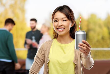 asian woman with can drink over rooftop party