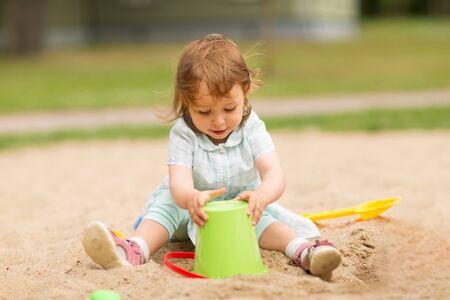 little baby girl plays with toys in sandbox Reklamní fotografie