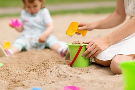 mother playing with baby daughter in sandbox