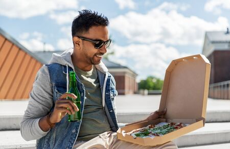 indian man with pizza and drinking beer outdoors