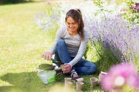 woman filling pots with soil at summer garden Banque d'images - 127631420