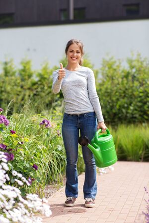 Gardening and people concept - Happy young woman watering flowers at summer garden