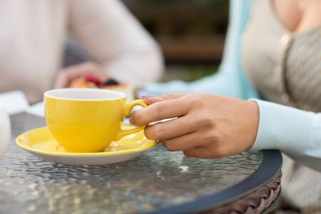 hand of woman drinking tea at outdoor cafe
