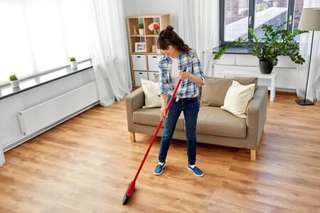 asian woman with broom sweeping floor and cleaning Foto de archivo