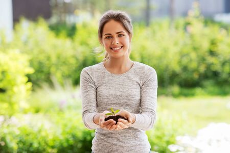 woman holding plant growing in handful of soil Stock Photo