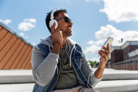Man with smartphone and headphones on roof top 스톡 콘텐츠