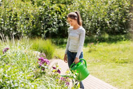 Young woman watering flowers at garden