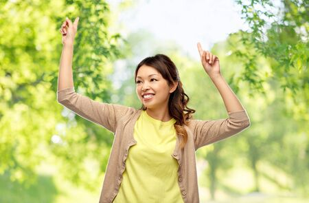 asian woman dancing over green natural background
